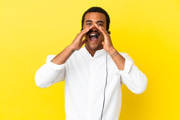 Afro-amerikaanse telemarketeer man aan het werk met een headset over geïsoleerde gele achtergrond schreeuwen en iets aankondigen