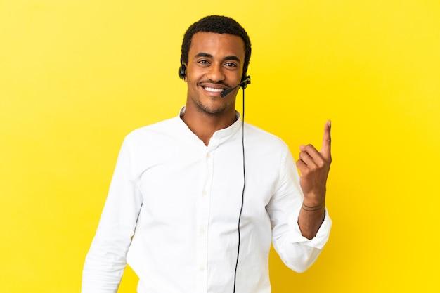 Afro-amerikaanse telemarketeer man aan het werk met een headset over geïsoleerde gele achtergrond wijzend met de wijsvinger een geweldig idee