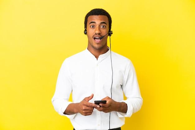 Afro-amerikaanse telemarketeer man die met een headset over geïsoleerde gele achtergrond werkt, verrast en stuurt een bericht