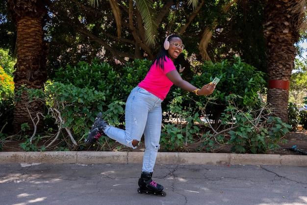 Afro-amerikaanse tiener die een foto maakt met de mobiele telefoon tijdens het schaatsen