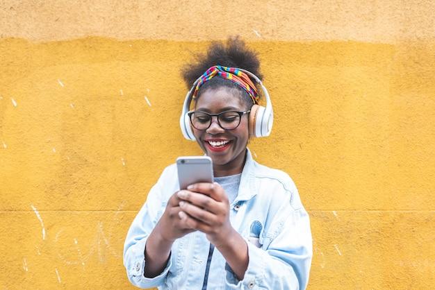 Afro-amerikaanse tiener met behulp van mobiele telefoon buitenshuis.