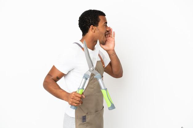 Afro-amerikaanse tuinman man met snoeischaar over geïsoleerde witte achtergrond schreeuwen met mond wijd open naar de zijkant