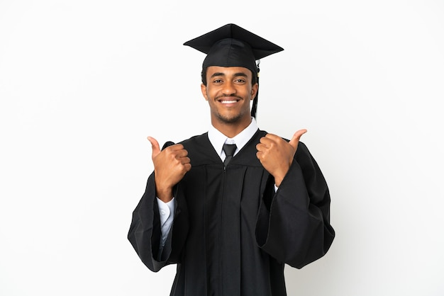Afro-amerikaanse universitair afgestudeerde man over geïsoleerde witte achtergrond met duim omhoog gebaar en lachend