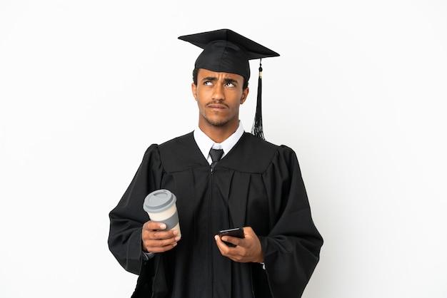 Afro-amerikaanse universitair afgestudeerde man over geïsoleerde witte achtergrond met koffie om mee te nemen en een mobiel terwijl hij iets denkt