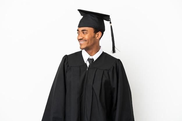 Afro-amerikaanse universitair afgestudeerde man over geïsoleerde witte achtergrond op zoek naar kant
