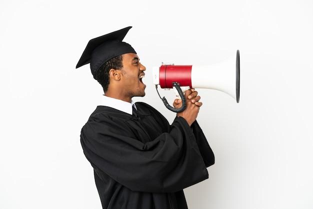 Afro-amerikaanse universitair afgestudeerde man over geïsoleerde witte achtergrond schreeuwen door een megafoon