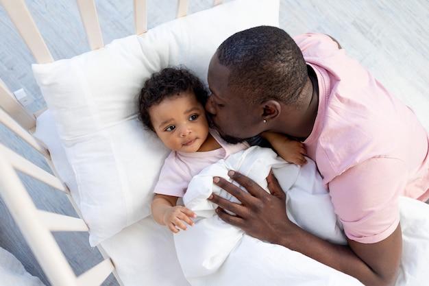 Afro-amerikaanse vader kust en knuffelt zoontje in wieg voordat hij naar bed gaat