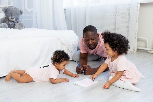 Afro-amerikaanse vader leert kinderen thuis potloden op de grond tekenen