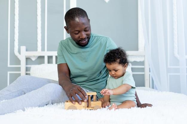 Afro-amerikaanse vader met zoontje spelen op het bed thuis met een houten speelgoedauto, gelukkige familie, vaderdag