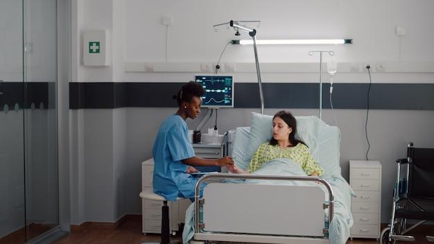 Afro-amerikaanse verpleegster controleert zieke vrouw die de pols analyseert met behulp van een medische oximeter die op de ziekenhuisafdeling werkt