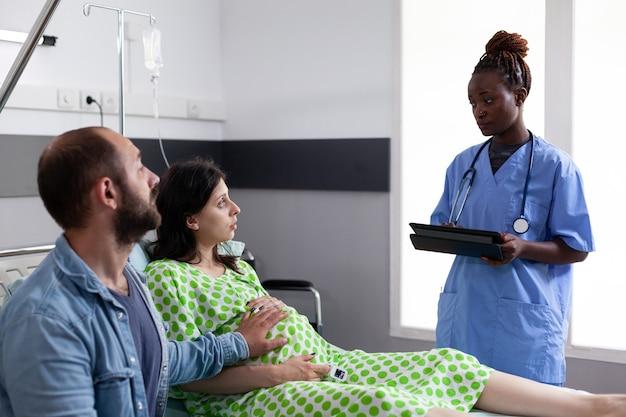 Afro-amerikaanse verpleegster die de gezondheidszorg van zwangere vrouw bewaakt