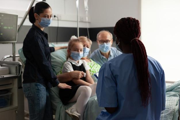 Afro-amerikaanse verpleegster die oudere oudere vrouw volgt na klinische chirurgie