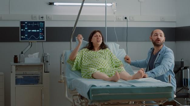 Afro-amerikaanse verpleegster die zwangere patiënt helpt met pijnlijke bevalling