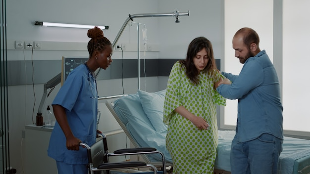 Afro-amerikaanse verpleegster die zwangere vrouw in rolstoel neemt