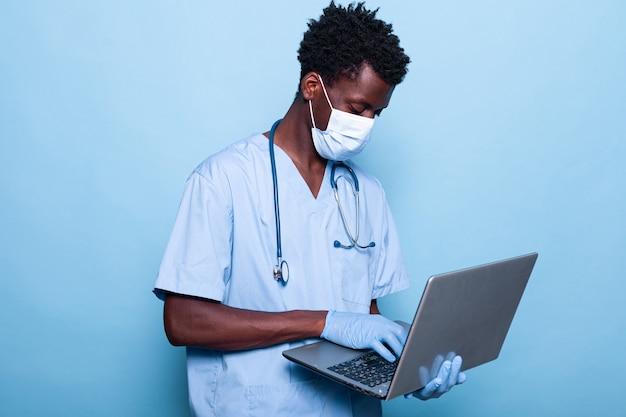 Afro-amerikaanse verpleegster met uniforme laptop