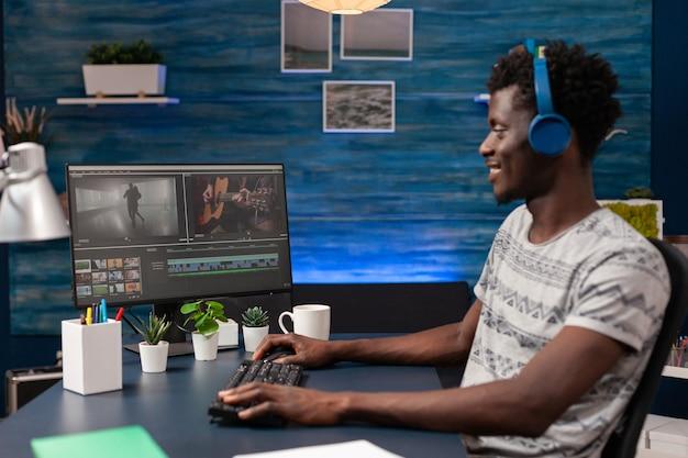 Afro-amerikaanse videograaf met headset die videofilmmontage bewerkt
