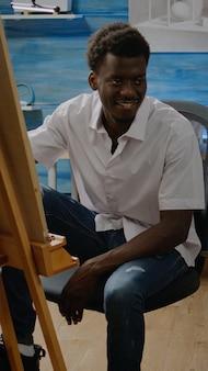 Afro-amerikaanse volwassene die in de tekening van de kunstwerkstudio zit