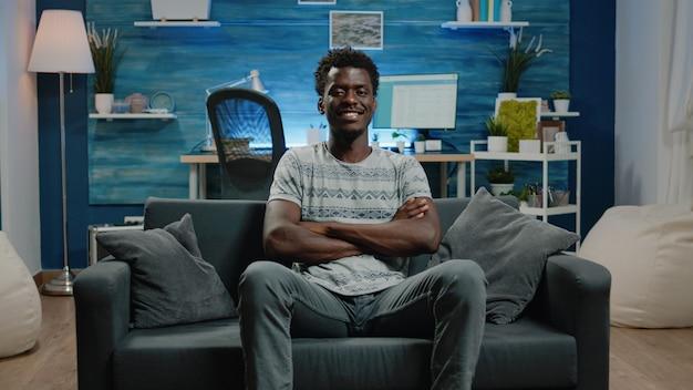 Afro-amerikaanse volwassene die op de bank zit en naar de camera kijkt
