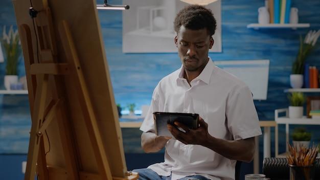 Afro-amerikaanse volwassene met artistieke vaardigheden met behulp van digitale tablet