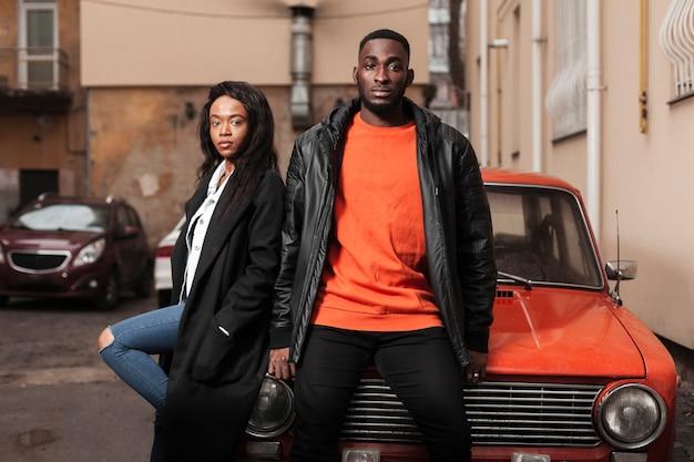 Afro-amerikaanse vrienden die op auto leunen