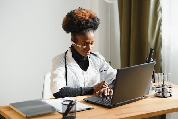 Afro-amerikaanse vrouw arts op de werkplek in het ziekenhuis.