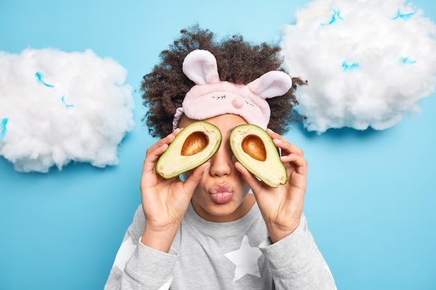 Afro-amerikaanse vrouw bedekt ogen met helften van avocado houdt lippen afgerond en maakt voedzaam gezichtsmasker draagt pyjama en slaapmasker geïsoleerd op blauw