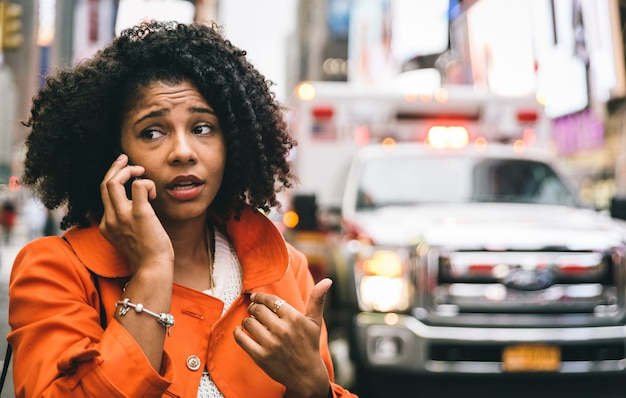 Afro-amerikaanse vrouw die 911 in de stad van new york roept. concept over auto-ongelukken en noodsituaties