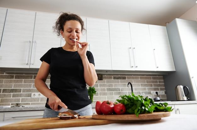 Afro-amerikaanse vrouw die achter een aanrecht in de keuken staat en rauwe paddenstoelen proeft terwijl ze ingrediënten voor pizza hakt