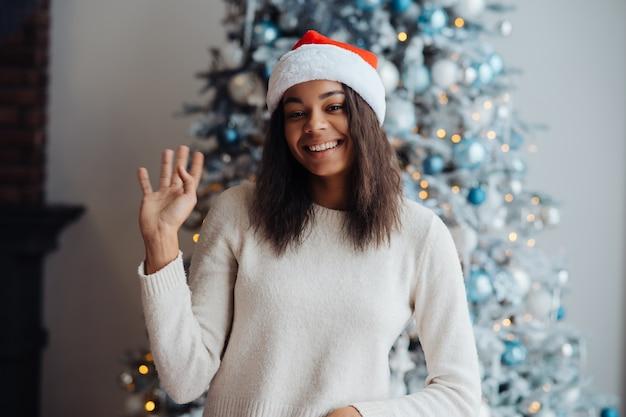 Afro-amerikaanse vrouw die de camera thuis bekijkt