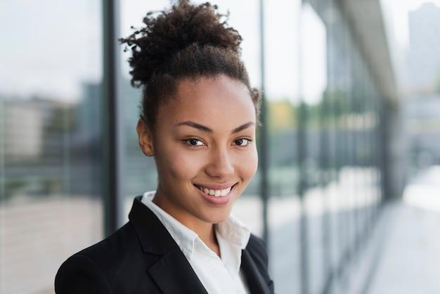 Afro amerikaanse vrouw die dicht omhoog glimlacht