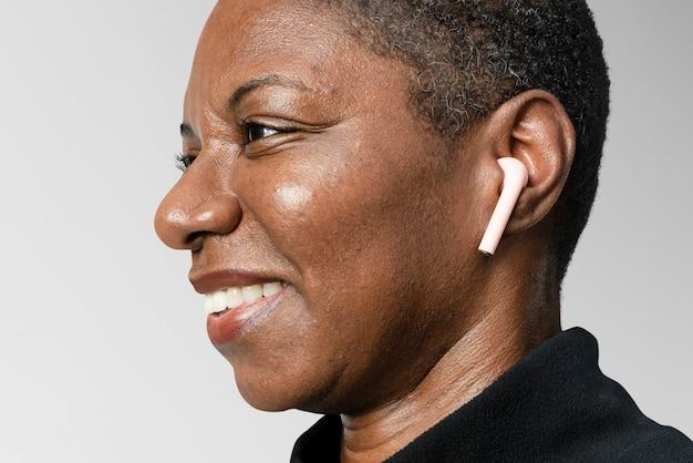 Afro-amerikaanse vrouw die draadloze oordopjes draagt