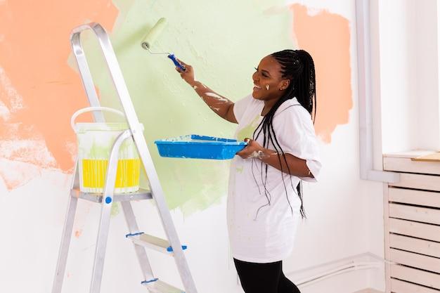 Afro-amerikaanse vrouw die een appartement schildert. renovatie, reparatie en herinrichting concept.