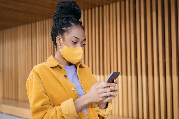 Afro-amerikaanse vrouw die een beschermend gezichtsmasker draagt via mobiele telefooncommunicatie online