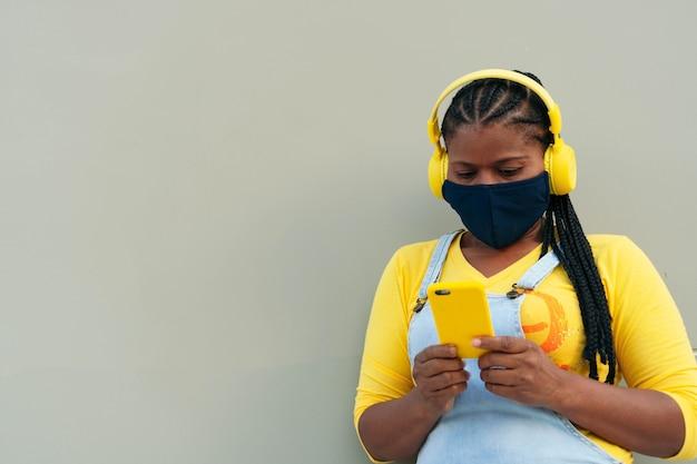 Afro-amerikaanse vrouw die een beschermend masker draagt en een bericht typt met haar smartphone.