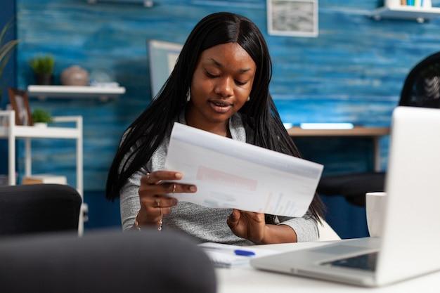 Afro-amerikaanse vrouw die een financieel grafiekdocument analyseert dat op afstand werkt bij marketingpresentatrion