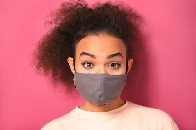 Afro-amerikaanse vrouw die een gezichtsmasker draagt om covid-19 te voorkomen