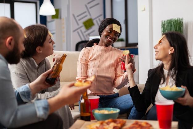 Afro-amerikaanse vrouw die een gokspel speelt met vrienden na het werk op kantoor. multi-etnische groep werknemers raadt imitatie voor leuke vrolijke activiteit tijdens het eten en drinken van bier