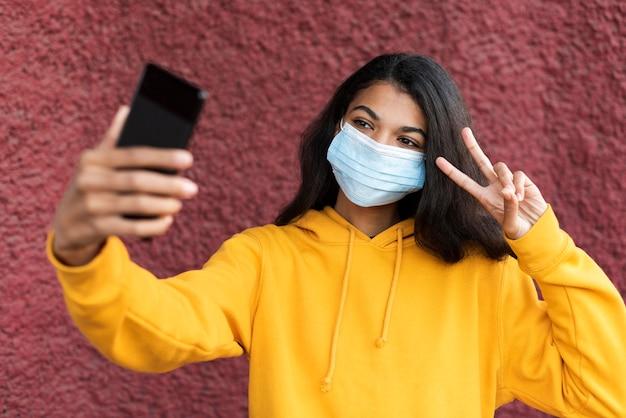 Afro-amerikaanse vrouw die een medisch masker draagt en een selfie neemt