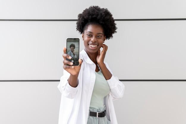 Afro-amerikaanse vrouw die een selfie maakt met haar smartphone