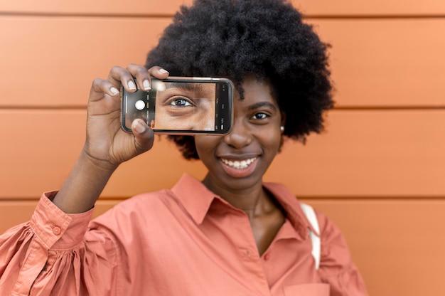 Afro-amerikaanse vrouw die een selfie van haar oog maakt