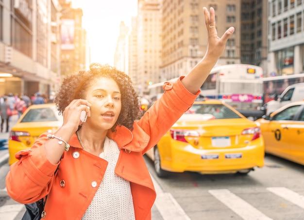 Afro-amerikaanse vrouw die een taxi in new york dichtbij het vierkante district van time roept.