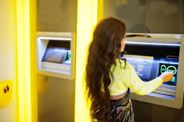 Afro-amerikaanse vrouw die geld opneemt uit een geldautomaat, atm-concept.
