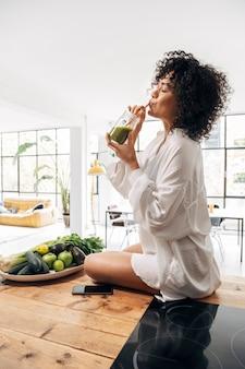 Afro-amerikaanse vrouw die groen sap drinkt met bamboestro verticaalgezonde levensstijlkopieer ruimte