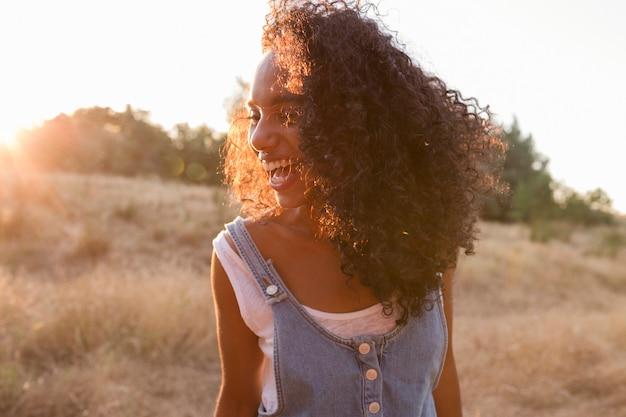 Afro-amerikaanse vrouw die lacht bij zonsondergang