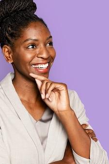 Afro-amerikaanse vrouw die lacht met de hand op de kin