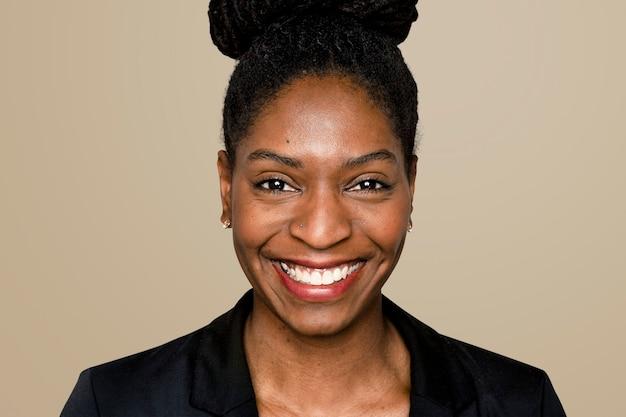 Afro-amerikaanse vrouw die lacht op beige achtergrond