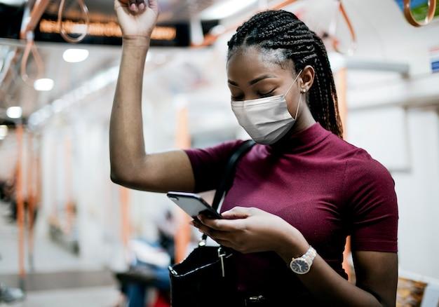 Afro-amerikaanse vrouw die masker draagt in de bus tijdens het gebruik van het openbaar vervoer in het nieuwe normaal