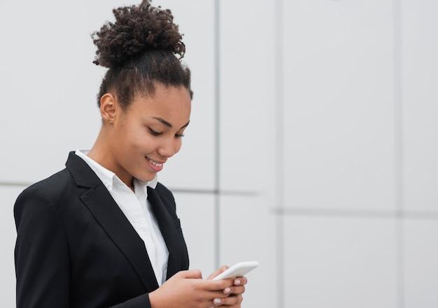 Afro-amerikaanse vrouw die telefoon controleert