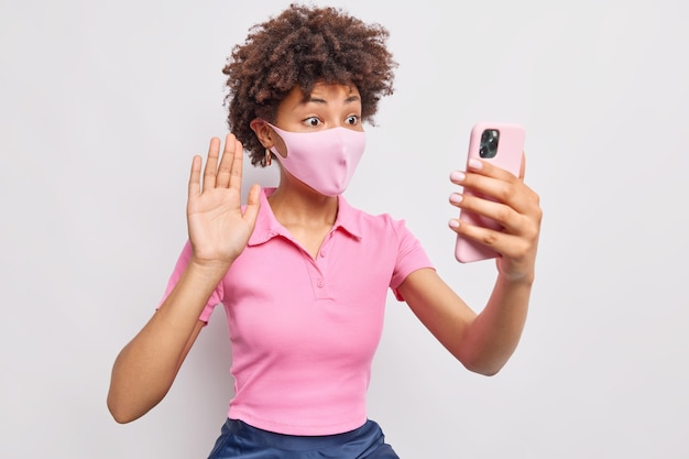 Afro-amerikaanse vrouw die tijdens de pandemie van het coronavirus in zelfisolatie zit, draagt een beschermend gezichtsmasker en maakt video-oproep golven palm in hallo gebaar houdt smartphone vooraan poses tegen witte muur