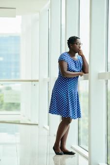 Afro-amerikaanse vrouw die zich door venster in bureau bevindt en uit kijkt